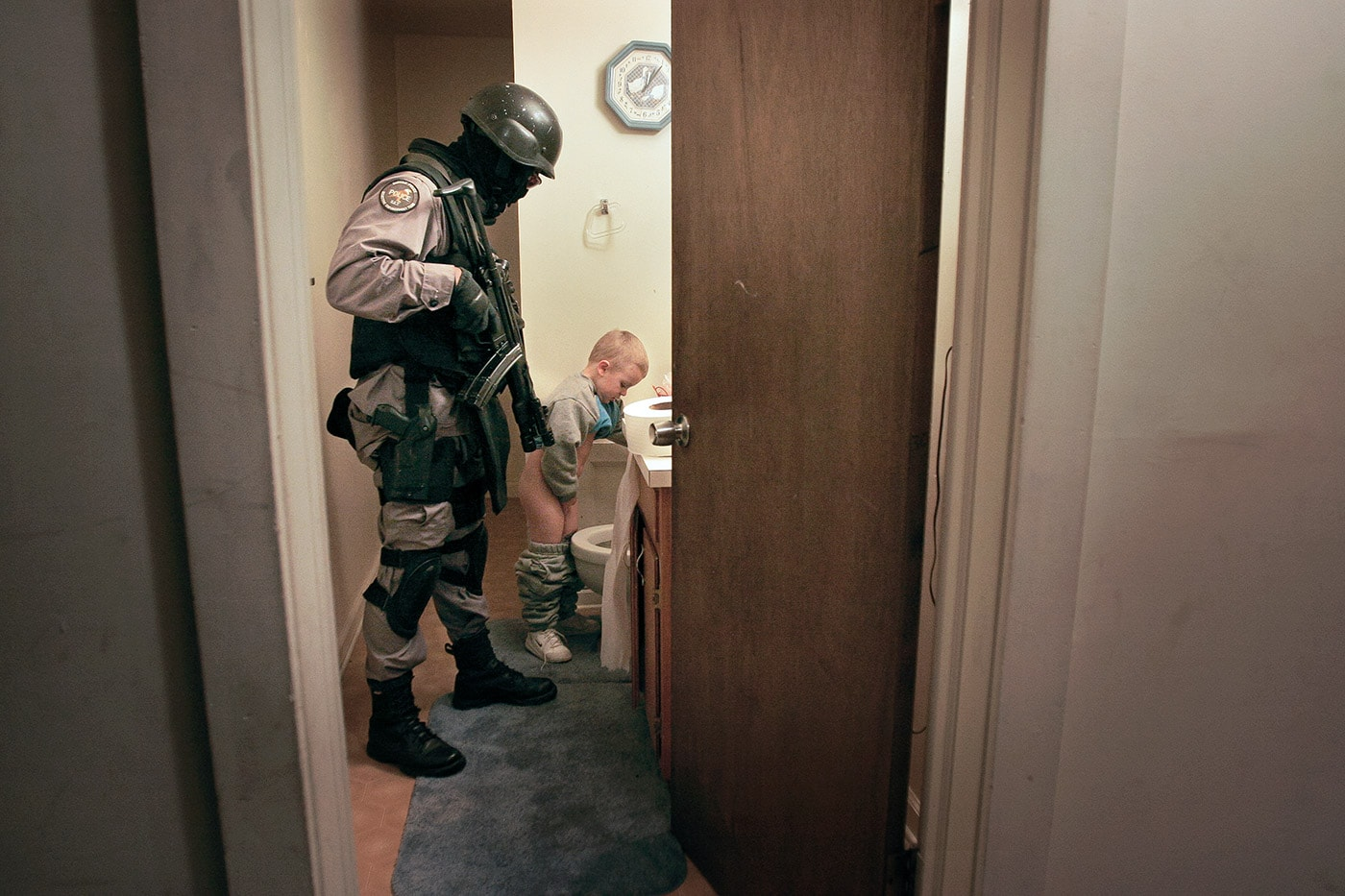 A Durham Police Department Selective Enforcement Team officer escorts a child to the bathroom after a drug raid. His mother was detained during the search in the house and was unable to tend to him.