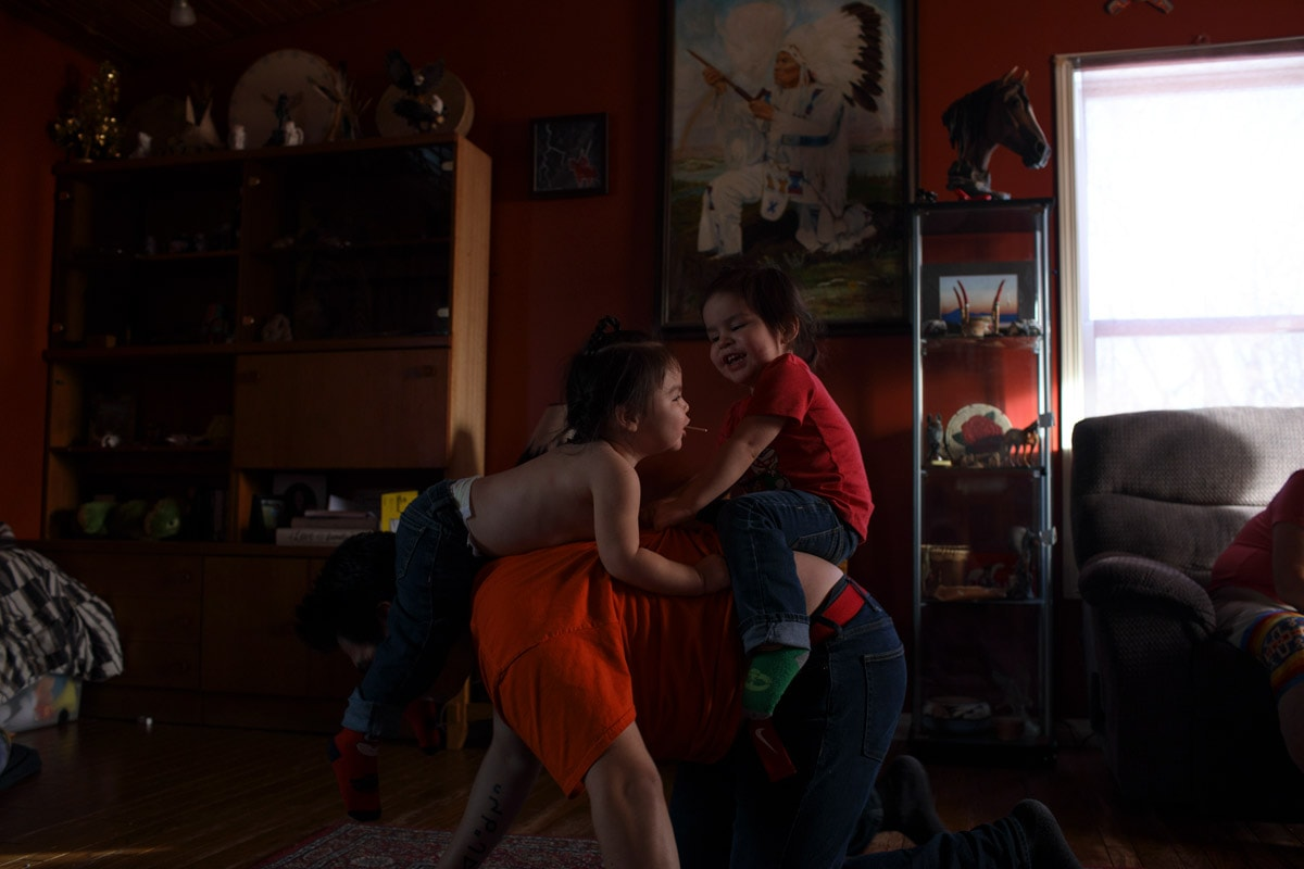 Dylan plays with his two sons in his parents living room on the Maskwacis reservation.